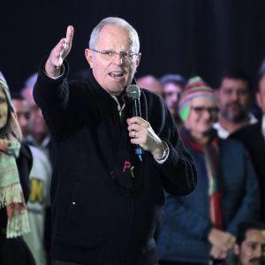 Silmälasipäinen mies pitelee mikrofonia ja puhuu, osoittaa samalla toisellaan kädellään etuviistoon. Taustalla on yleisöä, mm. perinteiseen perulaiseen lakkiin pukeutunut nainen.