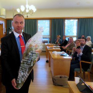 Mies keskellä salia kukkakimppu käsissään