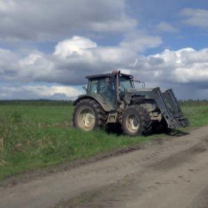 Traktori ajaa pellolta tielle.