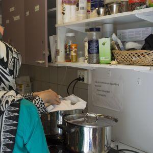 Huivipäiset naiset laittavat ruokaa.