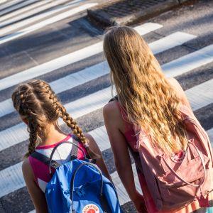 Kaksi lasta kävelee suojatiellä.