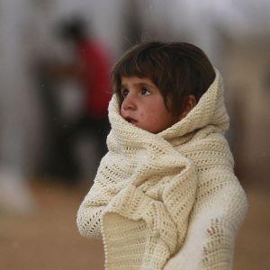 Syyrialainen pakolaistyttö  kääriytynenäänä villahuopaan pakolaisleirissä Turkissa.