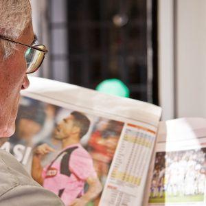 Iäkäs mies lukee lehteä.