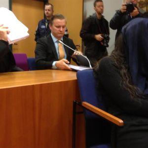 Syytetyt oikeussalissa, nainen on peittänyt kasvonsa huivilla, mies paperinivaskalla.