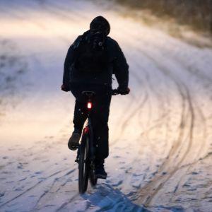 Pyöräilijä lumisella tiellä.