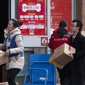 Kiinalaiset verkkokaupan työntekijät kantavat paketteja.