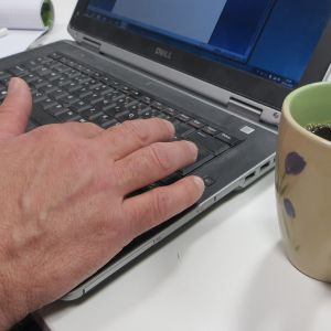 Mies tekee etätyötä tietokoneella.