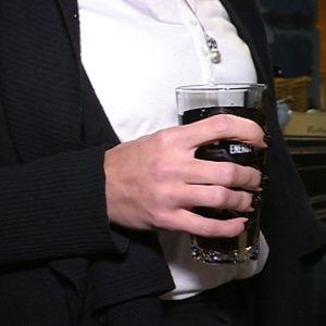 Nainen pitelee baarissa juomalasia kädessään