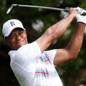 Tiger Woods katsoo golflyöntinsä perään.