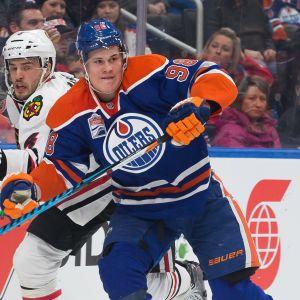Edmontonin Jesse Puljujärvi kamppailee NHL-kaukalossa Chicago-puolustaja Niklas Hjalmarssonin kanssa.