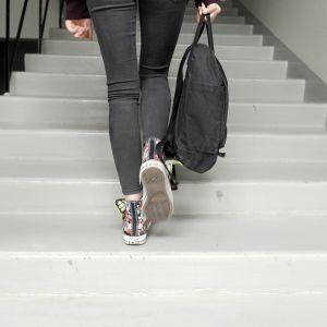 Nuori kiipeää reppu kädessään portaita ylöspäin.
