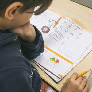 Poika tekee matematiikan tehtäviä.