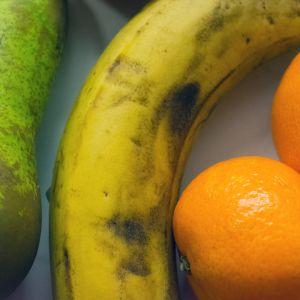 Banaani, päärynä ja mandariineja pöydällä.