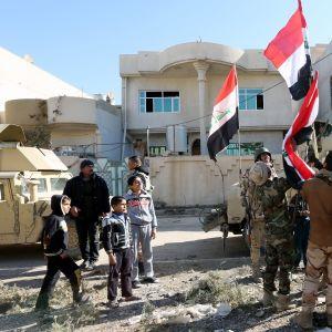 Sotilaat pystyttävät Irakin lippua siviilien katsellessa.