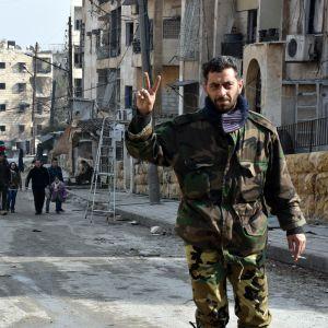 Syyrialainen sotilas näyttää voitonmerkkiä.