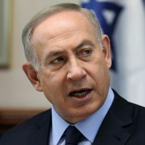Netanjahu puhuu tummassa puvussa, vaaleansinisessä kauluspaidassa, tummansininen kravatti kaulassaan. Taustalla näkyy Israelin lippu.
