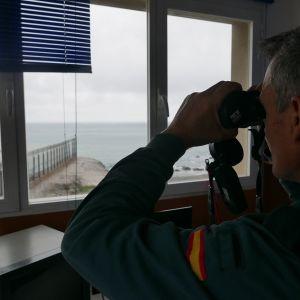 Vartiotorinissa oleva rajapoliisi katsoo kiikareille merelle, ulkona näkyy teräsaita, rantaa ja merta.
