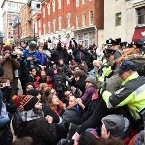 Joukko aktivisteja istuu maassa. Poliisi kantaa yhtä naista. Ympärillä on kuvaajia.