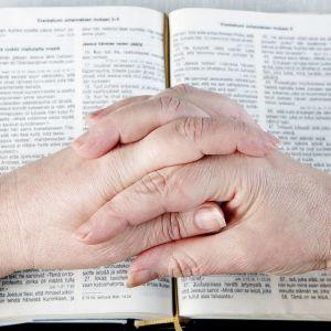 Naisen kädet ristissä raamatun päällä.