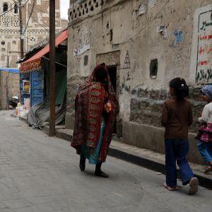 katunäkymä Sanaassa, kaksi lasta ja nainen kävelevät kadulla