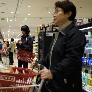 Japanilaisnaisia supermarketissa ostoskärryjen ja -korien kanssa.
