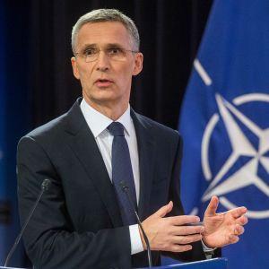 Stoltenberg taustallaan Naton lippu