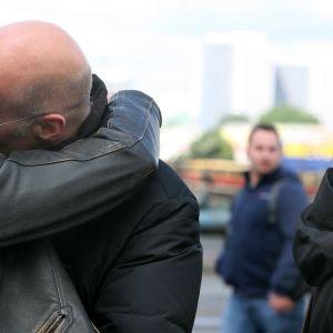 Kaksi miestä suutelee kadulla