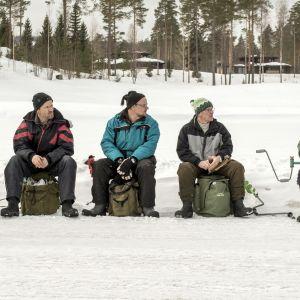 Miehet odottavat pilkkisojen avajaisia järven jäällä.
