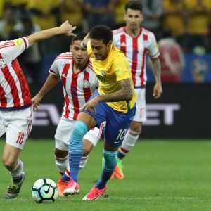 Brasilian Neymar vie Paraguayn pelaajia.