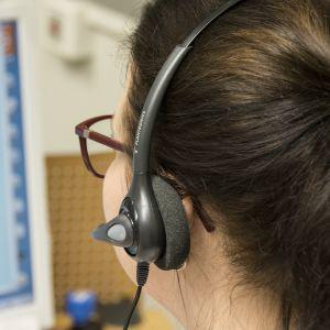 Anonyymi nainen puhuu headset-mikrofoniin.