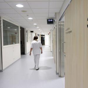 Hoitaja kävelee käytävällä.