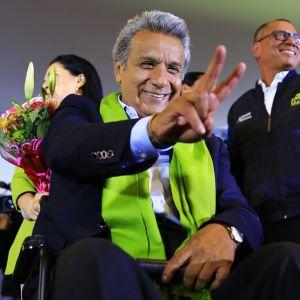 Ehdokas Lenin Moreno katsoo kameraan ja näyttää rauhan merkkiä yleisölle.