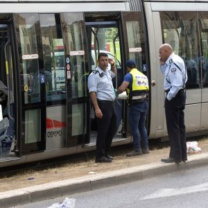 Pysähdyksissä oleva raitiovaunu. Joukko sinipaitaisia poliiseja ja keltaisiin huomioliiveihin pukeutuneita työntekijöitä tutkii vaunua, jonka ovet ovat auki.