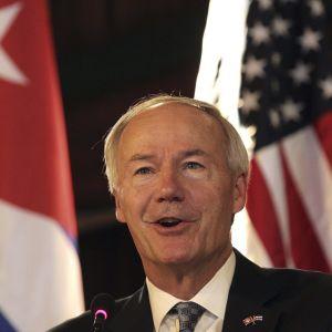 Asa Hutchinson puhuu mikrofoniin Havannassa, takana Kuuban ja Yhdysvaltain liput.