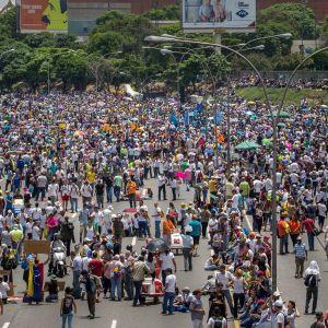 Ihmisiä mielenosoituksessa Venezuelan kadulla.