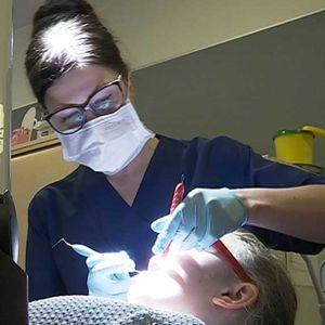 Suuhygienisti Jaana Ainali tarkastaa potilaan hampaat Ylikiimingin koululla.