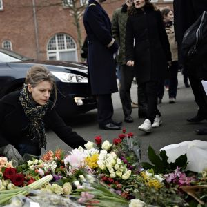 Nainen laskee kukkia uhrien muistoksi.