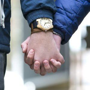 Miehet pitävät toisiaan kädestä