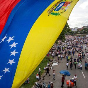 Etualalla Venezuelan puna-sini-keltainen lippu, takana ihmisjoukko