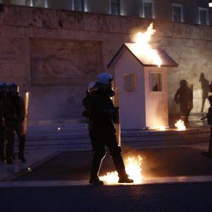 Mellakkapoliisit partioivat tuntemattoman sotilaan haudalla Ateenassa.