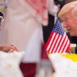 Abu Dhabin kruununprinssi ja Trump kättelevät. Etualalla pöydällä on pieni Yhdysvaltain lippu.