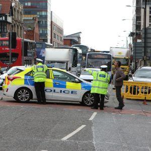 Poliisiauto poikittain kadulla, takana näkyy linja-autoja ja kuorma-autoja kadun täydeltä.