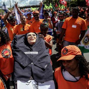 Brasilialaisia mielenosoituksessa, oranssit t-paidat ja presidentistä tehty iso nukke