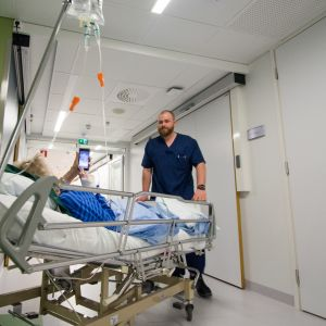 Lääkintävahtimestari työntää sairaalasängyssä kännykkää käyttävää iäkästä naista.