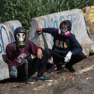Kaksi mielenosoittajaa kyyhöttää kaasunaamarit kasvoilla betoniporsaiden edessä.
