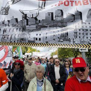 """Mielenosoittajajoukko marssii kadulla. Ensimmäisessä rivissä olevat kantavat suurta plakaattia, johon on kuvattu harmaita kerrostaloja. Julisteessa lukee punaisilla kirjaimilla """"protiv!"""" eli """"vastaan!"""""""
