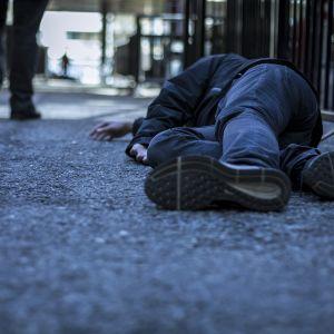Mies makaa maassa ja toinen kävelee pois päin