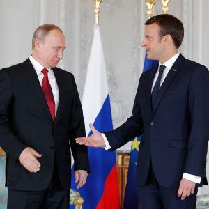 Putin katsoo Macronin kättä.