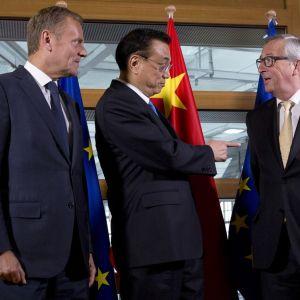 Donald Tusk, Li Keqiang ja Jean-Claude Juncker puhuvat. Taustalla näkyvät Kiinan ja EU:n liput.