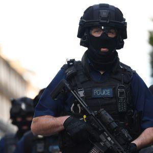 Aseistettuja poliiseja London Bridgen lähellä Lontoossa sunnuntaina.